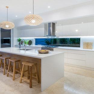 Maritim inredning av ett stort kök, med en undermonterad diskho, släta luckor, vita skåp, vitt stänkskydd, fönster som stänkskydd, rostfria vitvaror, en köksö och beiget golv