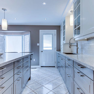 Mid-sized transitional l-shaped separate kitchen in Toronto with an undermount sink, raised-panel cabinets, white cabinets, quartz benchtops, beige splashback, porcelain splashback, stainless steel appliances, ceramic floors and with island.