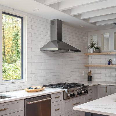 Inspiration for a mid-sized transitional u-shaped medium tone wood floor and brown floor open concept kitchen remodel in Raleigh with an undermount sink, recessed-panel cabinets, blue cabinets, quartzite countertops, white backsplash, subway tile backsplash, stainless steel appliances, an island and white countertops