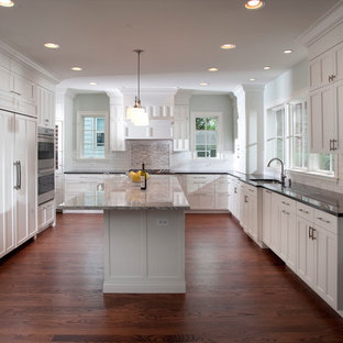Large modern kitchen appliance - Inspiration for a large modern u-shaped dark wood floor kitchen remodel in Chicago with an undermount sink, recessed-panel cabinets, white cabinets, granite countertops, white backsplash, subway tile backsplash, white appliances and an island