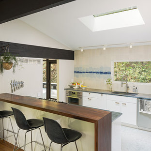 Midcentury single-wall open plan kitchen in Philadelphia with an undermount sink, flat-panel cabinets, white cabinets, wood benchtops, beige splashback, ceramic splashback, stainless steel appliances, marble floors, with island and white floor.