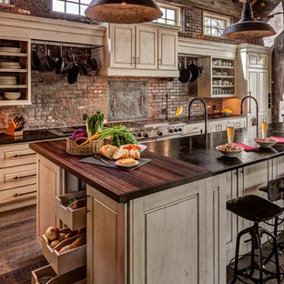 Large rustic open concept kitchen designs - Inspiration for a large rustic l-shaped dark wood floor and brown floor open concept kitchen remodel in Denver with raised-panel cabinets, paneled appliances, an island, an integrated sink, beige cabinets, red backsplash, brick backsplash and black countertops
