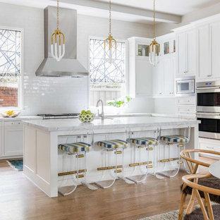 ダラスのビーチスタイルのおしゃれなキッチン (シェーカースタイル扉のキャビネット、白いキャビネット、白いキッチンパネル、サブウェイタイルのキッチンパネル、シルバーの調理設備、無垢フローリング、白いキッチンカウンター) の写真