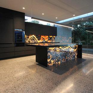 Выдающиеся фото от архитекторов и дизайнеров интерьера: параллельная кухня-гостиная среднего размера в стиле модернизм с черными фасадами, оранжевым фартуком, фартуком из каменной плиты, черной техникой, островом и черной столешницей
