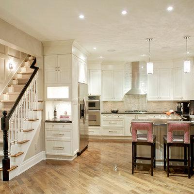 Large transitional u-shaped light wood floor kitchen photo in Toronto with recessed-panel cabinets, white cabinets, beige backsplash, stainless steel appliances, stone tile backsplash and quartz countertops