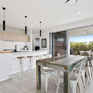 Inspiration for a mid-sized contemporary galley open plan kitchen in Brisbane with flat-panel cabinets, quartz benchtops, grey splashback, ceramic splashback, stainless steel appliances, with island, an integrated sink, light wood cabinets and grey floor.