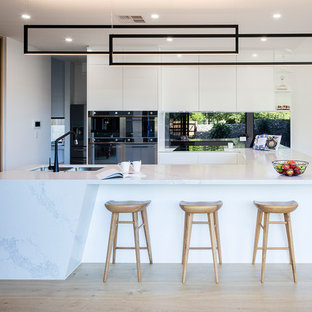 Photo of a mid-sized contemporary u-shaped open plan kitchen in Brisbane with a double-bowl sink, white cabinets, quartzite benchtops, metallic splashback, mirror splashback, black appliances, light hardwood floors, no island, beige floor, white benchtop and flat-panel cabinets.