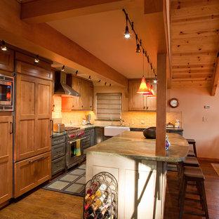 Exempel på ett mellanstort rustikt kök, med en rustik diskho, luckor med infälld panel, skåp i mellenmörkt trä, granitbänkskiva, beige stänkskydd, stänkskydd i tunnelbanekakel, integrerade vitvaror, mellanmörkt trägolv och en köksö