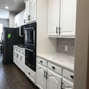 Design ideas for a mid-sized modern galley eat-in kitchen in Dallas with an undermount sink, louvered cabinets, white cabinets, quartz benchtops, grey splashback, ceramic splashback, black appliances, ceramic floors, no island, brown floor and white benchtop.
