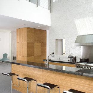 Moderne Küche mit Küchengeräten aus Edelstahl, flächenbündigen Schrankfronten, hellen Holzschränken und Küchenrückwand in Weiß in Los Angeles