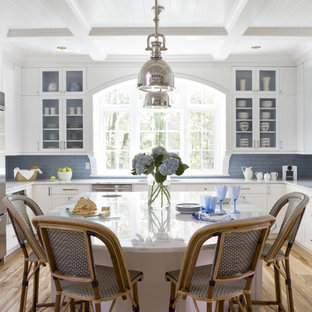 Large coastal eat-in kitchen inspiration - Example of a large beach style u-shaped light wood floor eat-in kitchen design in DC Metro with glass-front cabinets, marble countertops, blue backsplash, stainless steel appliances, an island, white cabinets and subway tile backsplash