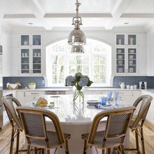 Idéer för stora maritima kök, med luckor med glaspanel, marmorbänkskiva, blått stänkskydd, rostfria vitvaror, ljust trägolv, en köksö, vita skåp och stänkskydd i tunnelbanekakel