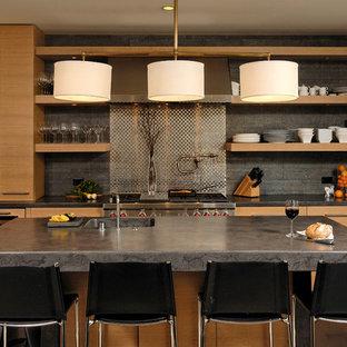 Modelo de cocina comedor de galera, actual, de tamaño medio, con puertas de armario de madera clara, salpicadero metalizado, salpicadero de metal, electrodomésticos de acero inoxidable, una isla, fregadero integrado, armarios con paneles lisos, encimera de granito y suelo de madera oscura
