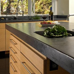 Ispirazione per una cucina design di medie dimensioni con ante lisce, ante in legno chiaro, top in granito, elettrodomestici in acciaio inossidabile, isola, lavello integrato, paraspruzzi con piastrelle di metallo, parquet scuro e paraspruzzi a effetto metallico