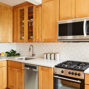 Small mid-century modern eat-in kitchen designs - Eat-in kitchen - small mid-century modern l-shaped porcelain floor eat-in kitchen idea in New York with an undermount sink, shaker cabinets, orange cabinets, quartzite countertops, white backsplash, ceramic backsplash, stainless steel appliances and an island