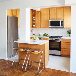 Imagen de cocina comedor en L, vintage, pequeña, con fregadero bajoencimera, armarios estilo shaker, puertas de armario naranjas, encimera de cuarcita, salpicadero blanco, salpicadero de azulejos de cerámica, electrodomésticos de acero inoxidable, suelo de baldosas de porcelana y una isla