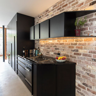Design ideas for a mid-sized contemporary eat-in kitchen in Sydney with flat-panel cabinets, black cabinets and subway tile splashback.