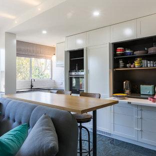 Пример оригинального дизайна: маленькая угловая кухня-гостиная в стиле неоклассика (современная классика) с врезной раковиной, фасадами с утопленной филенкой, белыми фасадами, столешницей из кварцевого агломерата, белым фартуком, фартуком из керамической плитки, техникой из нержавеющей стали, полом из линолеума и зеленым полом без острова