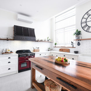 Inspiration for a large country u-shaped open plan kitchen in Sydney with a farmhouse sink, shaker cabinets, white cabinets, quartz benchtops, white splashback, ceramic splashback, coloured appliances, with island, grey floor and grey benchtop.