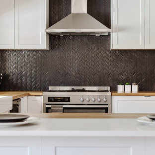 パースの大きいシャビーシック調のおしゃれなキッチン (エプロンフロントシンク、シェーカースタイル扉のキャビネット、白いキャビネット、木材カウンター、黒いキッチンパネル、モザイクタイルのキッチンパネル、シルバーの調理設備、竹フローリング、アイランドなし、茶色い床、茶色いキッチンカウンター) の写真