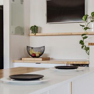 パースの大きいシャビーシック調のおしゃれなキッチン (エプロンフロントシンク、シェーカースタイル扉のキャビネット、白いキャビネット、木材カウンター、黒いキッチンパネル、モザイクタイルのキッチンパネル、シルバーの調理設備の、竹フローリング、アイランドなし、茶色い床、茶色いキッチンカウンター) の写真