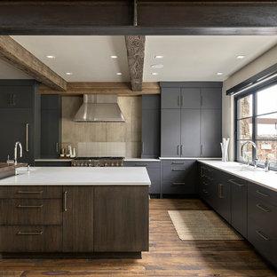 Exemple d'une grande cuisine américaine montagne en U avec un évier encastré, un placard à porte plane, des portes de placard grises, une crédence grise, un électroménager en acier inoxydable, un sol en bois brun, un îlot central, un sol marron et un plan de travail blanc.