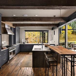 デンバーの大きいラスティックスタイルのおしゃれなキッチン (アンダーカウンターシンク、フラットパネル扉のキャビネット、グレーのキャビネット、グレーのキッチンパネル、パネルと同色の調理設備、無垢フローリング、茶色い床、白いキッチンカウンター) の写真