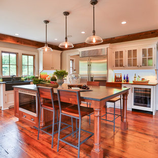 Design ideas for a large country u-shaped separate kitchen in Boston with a farmhouse sink, flat-panel cabinets, white cabinets, light hardwood floors, with island and solid surface benchtops.
