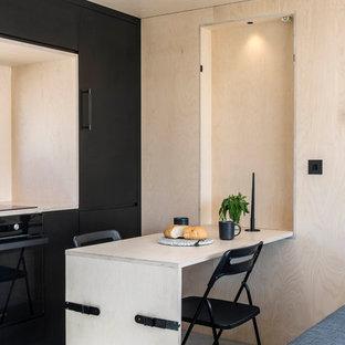 オックスフォードシャーの北欧スタイルのおしゃれなペニンシュラキッチン (フラットパネル扉のキャビネット、黒いキャビネット、ベージュキッチンパネル、木材のキッチンパネル、黒い調理設備、コンクリートの床、グレーの床、ベージュのキッチンカウンター) の写真