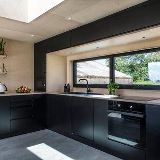 Skandinavische Küche in L-Form mit Einbauwaschbecken, flächenbündigen Schrankfronten, schwarzen Schränken, Arbeitsplatte aus Holz, Rückwand-Fenster, schwarzen Elektrogeräten, Betonboden, grauem Boden und beiger Arbeitsplatte in Oxfordshire