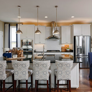 Expansive traditional single-wall open plan kitchen in DC Metro with a double-bowl sink, shaker cabinets, white cabinets, solid surface benchtops, white splashback, subway tile splashback, stainless steel appliances, vinyl floors, with island and brown floor.