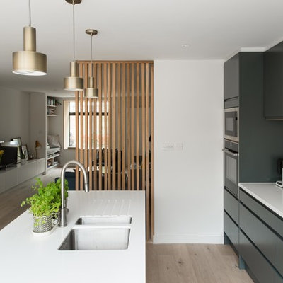 Example of a minimalist single-wall light wood floor eat-in kitchen design in London with a drop-in sink, flat-panel cabinets, black cabinets, quartzite countertops, an island and white countertops