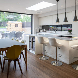 Inspiration for a large contemporary galley kitchen/diner in Essex with a submerged sink, flat-panel cabinets, beige cabinets, black splashback, glass sheet splashback, integrated appliances, medium hardwood flooring, an island, brown floors and beige worktops.