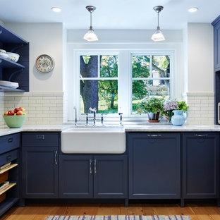Große Klassische Küche in U-Form mit Landhausspüle, Schrankfronten mit vertiefter Füllung, blauen Schränken, Marmor-Arbeitsplatte, Küchenrückwand in Weiß, Küchengeräten aus Edelstahl, braunem Holzboden und Kücheninsel in Minneapolis