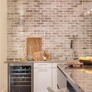 アトランタの広いコンテンポラリースタイルのおしゃれなキッチン (シングルシンク、シェーカースタイル扉のキャビネット、白いキャビネット、クオーツストーンカウンター、マルチカラーのキッチンパネル、レンガのキッチンパネル、シルバーの調理設備、淡色無垢フローリング、ベージュの床、グレーのキッチンカウンター) の写真