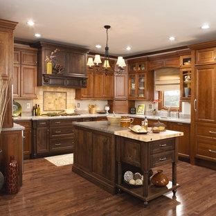 Große, Geschlossene Klassische Küche in U-Form mit Unterbauwaschbecken, profilierten Schrankfronten, hellbraunen Holzschränken, Quarzwerkstein-Arbeitsplatte, Küchenrückwand in Gelb, Rückwand aus Keramikfliesen, Elektrogeräten mit Frontblende, dunklem Holzboden, Kücheninsel, braunem Boden und grauer Arbeitsplatte in Minneapolis