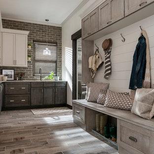 ミネアポリスの中くらいのラスティックスタイルのおしゃれなキッチン (シェーカースタイル扉のキャビネット、濃色木目調キャビネット、御影石カウンター、レンガのキッチンパネル、磁器タイルの床、ベージュの床) の写真