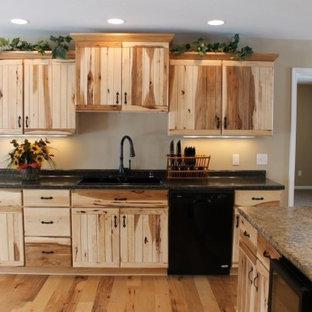 Imagen de cocina en U, rural, de tamaño medio, abierta, con fregadero de doble seno, puertas de armario de madera clara, encimera de laminado, electrodomésticos negros, suelo de madera clara y una isla
