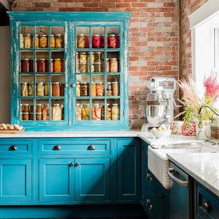 Inspiration för ett mycket stort lantligt kök, med en rustik diskho, luckor med glaspanel, skåp i slitet trä, stänkskydd i tegel, rostfria vitvaror, mörkt trägolv, bänkskiva i kvarts, en köksö och rött stänkskydd