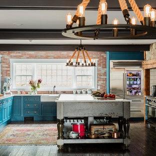 Bild på ett mycket stort lantligt kök, med en rustik diskho, luckor med glaspanel, turkosa skåp, bänkskiva i kvarts, rött stänkskydd, stänkskydd i tegel, rostfria vitvaror, mellanmörkt trägolv och en köksö