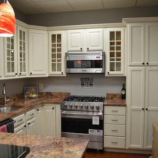 Foto di una piccola cucina ad U classica con lavello sottopiano, ante con bugna sagomata, ante bianche, top in granito, elettrodomestici in acciaio inossidabile, penisola e top arancione