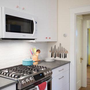 ボストンの小さいエクレクティックスタイルのおしゃれなキッチン (アンダーカウンターシンク、フラットパネル扉のキャビネット、白いキャビネット、クオーツストーンカウンター、白いキッチンパネル、セラミックタイルのキッチンパネル、シルバーの調理設備、淡色無垢フローリング、アイランドなし、ベージュの床、グレーのキッチンカウンター) の写真