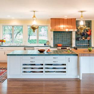 Inspiration pour une grande cuisine américaine traditionnelle en L avec un évier encastré, un placard à porte shaker, des portes de placard blanches, un plan de travail en carrelage, une crédence bleue, un électroménager encastrable, un sol en bois brun, un îlot central, une crédence en carreau de céramique et un plan de travail turquoise.