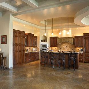 フェニックスの中サイズの地中海スタイルのおしゃれなキッチン (レイズドパネル扉のキャビネット、中間色木目調キャビネット、茶色いキッチンパネル、石タイルのキッチンパネル、パネルと同色の調理設備、トラバーチンの床、茶色い床) の写真