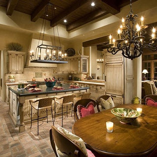 Large mediterranean u-shaped eat-in kitchen in Phoenix with a farmhouse sink, louvered cabinets, distressed cabinets, beige splashback, stone tile splashback, panelled appliances, brick floors, with island and multi-coloured floor.