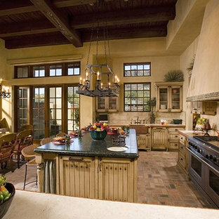 Photo of a large mediterranean u-shaped eat-in kitchen in Phoenix with a farmhouse sink, louvered cabinets, distressed cabinets, beige splashback, stone tile splashback, panelled appliances, brick floors, with island and multi-coloured floor.