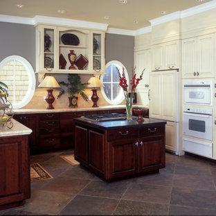 シアトルの中くらいの地中海スタイルのおしゃれなキッチン (ドロップインシンク、レイズドパネル扉のキャビネット、濃色木目調キャビネット、タイルカウンター、ベージュキッチンパネル、セラミックタイルのキッチンパネル、パネルと同色の調理設備、スレートの床) の写真