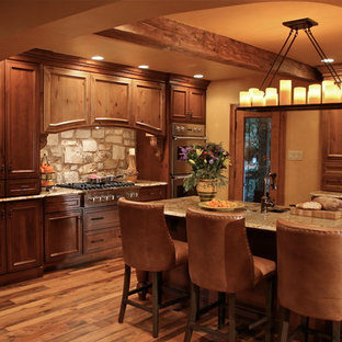 フィラデルフィアの大きい地中海スタイルのおしゃれなキッチン (御影石カウンター、シルバーの調理設備の、レイズドパネル扉のキャビネット、濃色木目調キャビネット、茶色いキッチンパネル、石タイルのキッチンパネル、濃色無垢フローリング、茶色い床) の写真