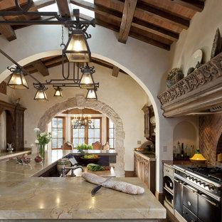 Mediterranean kitchen designs - Tuscan kitchen photo in San Francisco with black appliances