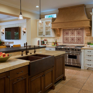 Inspiration for a large mediterranean l-shaped limestone floor and beige floor open concept kitchen remodel in Orange County with a farmhouse sink, recessed-panel cabinets, white cabinets, beige backsplash, stainless steel appliances, limestone backsplash, limestone countertops and an island